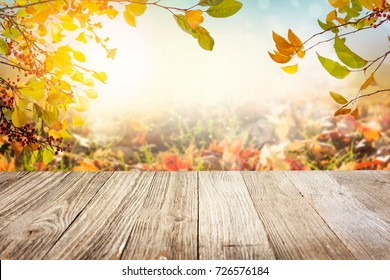 Wooden table with autumn leaves in sunny day background