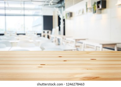 a wooden table with background of blurry modern cafe restaurant interior in a bright day light