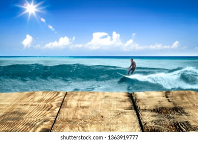 Wooden table background of free space for your decoration. Surfer on board with big waves on ocean. Summer blue sky with sun.