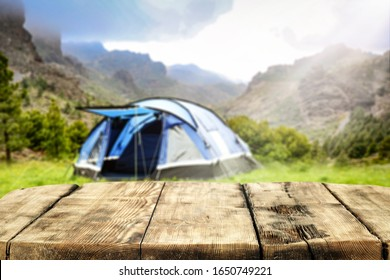 Wooden table background of free space for your decoration and blurred background of camping in mountains.