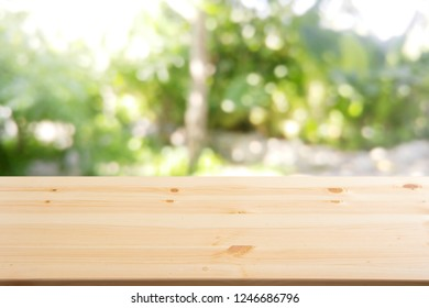 a wooden table with background of unfocused and blurry morning backyard