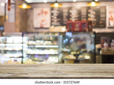 wooden table with bakery shop or coffee cafe blurred background