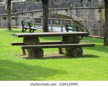 Wooden table and benches on green grass just by the bridge over the Doubs in Sainte-Ursanne (Jura)