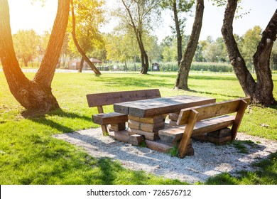 Wooden table with benches in the park, ready for barbecue and family gatherings