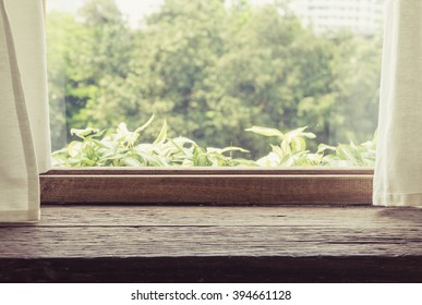 Wooden table beside vintage wood window and white curtain