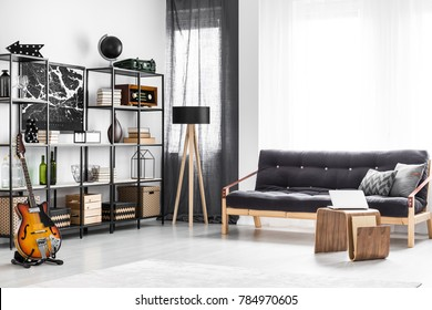 Wooden table and black sofa with cushions in bright guy's room interior with guitar, lamp and shelves