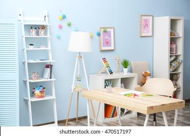 Wooden table in blue children room interior