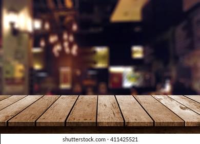 wooden table in blur restaurant lights background