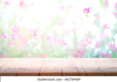 Wooden table with blurred abstract background of pink flower, For product display