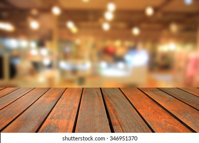 Wooden table and  blurred background of generic supermarket people walking shopping