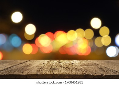 wooden table with blurred bokeh background of traffic light on road.