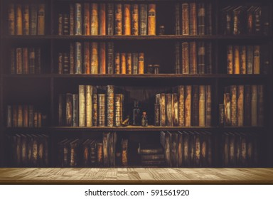 wooden table in blurred  Image Many old books on bookshelf in library