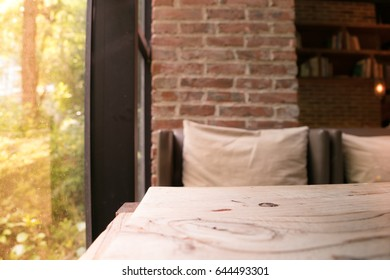 the wooden table and blurred sofa beside a window of coffee shop