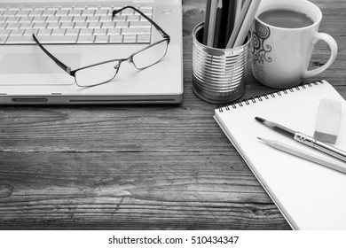 wooden table with brew mug, sketch book, eyeglasses, color pencil, pencil, rubber, tin can and laptop (selective focus and shallow dept of field)