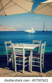 Wooden table and chairs by the sea, on the pier, in the distance you can see large and expensive yachts at sea