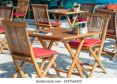 Wooden table and chairs in empty beach cafe next to sea. Close up. Island Koh Phangan, Thailand