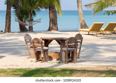 Wooden table and chairs in empty cafe next to the sea water on the tropical beach in island Koh Kood,Thailand. Close up