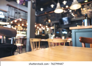 Wooden table and chairs in modern loft cafe with blur bokeh vintage background