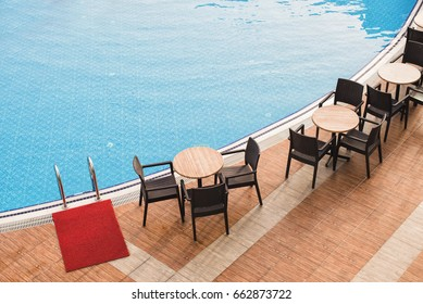 Wooden table and chairs near the pool.