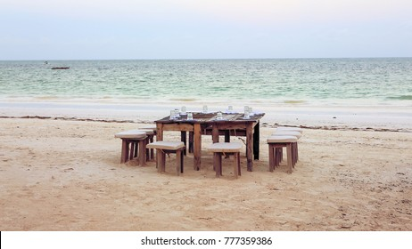 Wooden table and chairs on the beach.