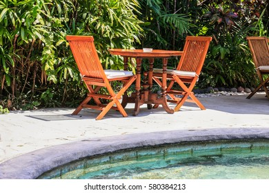 Wooden table and chairs in tropical balinese style near pool