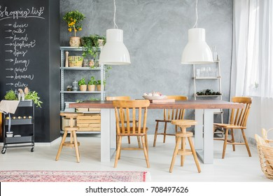 Wooden table and chalkboard wall in stylish dining room interior