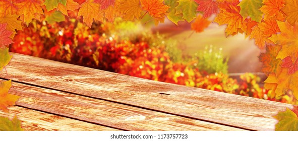Wooden table with colorful autumn leaves as background