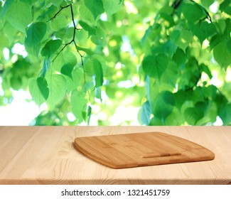 wooden table with cutting Board against green young leaves. background of the fake branches. empty space for your product. layout.