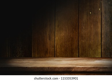 Wooden table in dark room background concept for advertising.