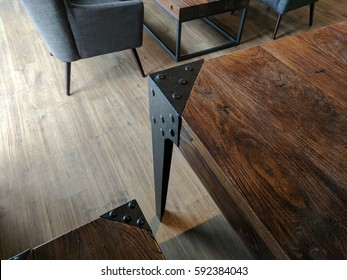 Wooden table / desk with black steel border and button pattern, and wooden bench set. The black coach sofa beside to the next. The floor is light brown wooden texture. All is in the restaurant cafe