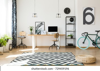 Wooden table with desktop efficient work area with bike, braided pouf on black and white carpet