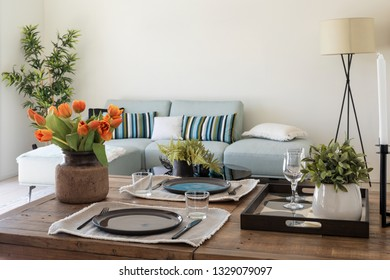 Wooden table detail with plates, cutlery and bunch of orange tulips. Modern design living room. Nobody inside
