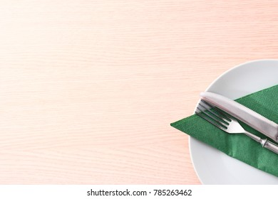 Wooden table with dish and cutlery.