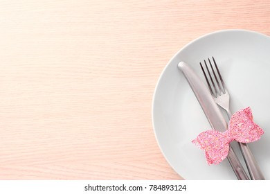 Wooden table with dish, cutlery and pink bow. Valentines day background.