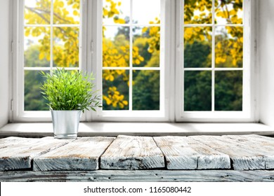 Wooden table of free space for your decoration and window background with autumn time.