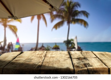 Wooden table of free space for your decoration and exotic landscape of sea palms and blue water. Sunset time.