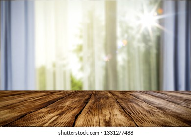 Wooden table of free space for your decoration. Blurred window background and spring time. Sunny day