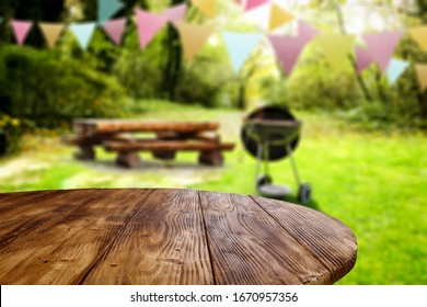 Wooden table of free space for your decoration and blurred background of park and spring time.Grill time and party.
