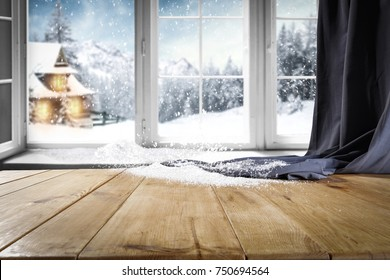 Wooden table with free space for your product or promotional text. Open window with snowfall. Landscape of winter forest mountains and small dock at the end of the village.
