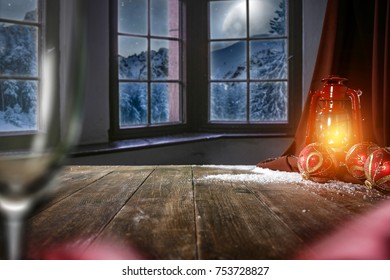 Wooden table of free space for your decoration. Window with view of mountains and moon at night. Christmas time decoration.