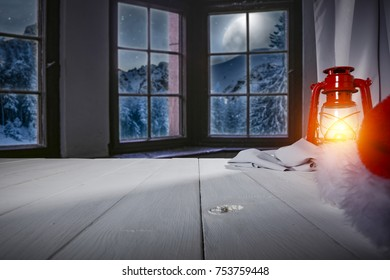 Wooden table of free space for your decoration. Background of window and view of mountains and moon on the sky with few stars. Santa claus home interior.