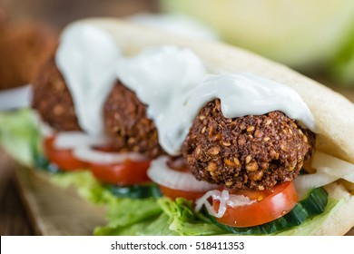 Wooden table with a fresh made Falafel Sandwich (selective focus; close-up shot)
