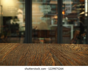 Wooden table in front of abstract blurred cafe, coffee shop background.