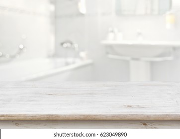 Wooden table in front of blurred bathroom interior as background.