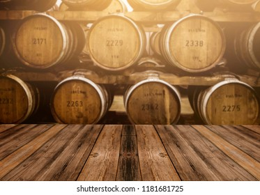Wooden table in front of blurred oak barrel background, background of whisky and wine
