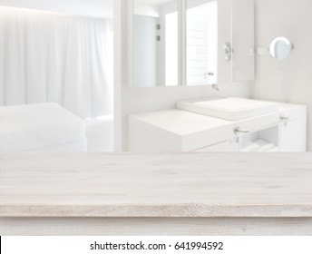 Wooden table in front of blurred resort room interior background