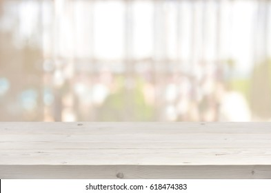 Wooden table in front of blurred transparent window curtain background