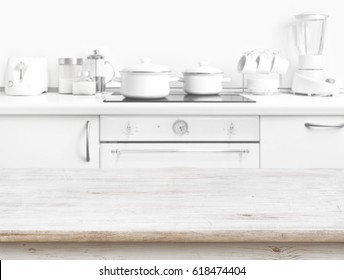 Wooden table in front of blurred white kitchen bench interior
