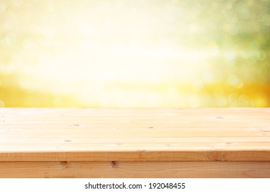 wooden table in front of defocused open view and bokeh lights. ready for product display