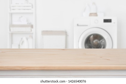 Wooden table in front of defocused washing machine and laundry